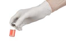 Medicinskt tema: doktors hand i en vit handske som rymmer en röd liten medicinflaska av flytande för injektionen som isoleras på  Fotografering för Bildbyråer