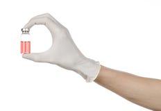 Medicinskt tema: doktors hand i en vit handske som rymmer en röd liten medicinflaska av flytande för injektionen som isoleras på  Royaltyfri Fotografi