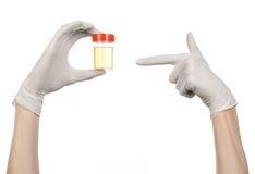 Medicinskt tema: doktors hand i vita handskar som rymmer en genomskinlig behållare med analysen av urin på en vit bakgrund Fotografering för Bildbyråer
