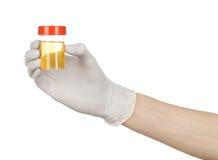 Medicinskt tema: doktors hand i vita handskar som rymmer en genomskinlig behållare med analysen av urin på en vit bakgrund Royaltyfri Bild