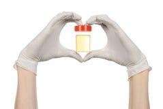 Medicinskt tema: doktors hand i vita handskar som rymmer en genomskinlig behållare med analysen av urin på en vit bakgrund Arkivfoton