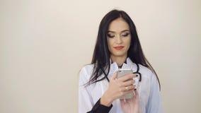 Medico abbastanza femminile che per mezzo del telefono cellulare su fondo 4K video d archivio