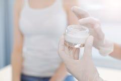 Medico abile che utilizza crema medica speciale nella clinica Fotografie Stock