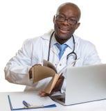 Medico africano che legge le cartelle sanitarie Fotografia Stock