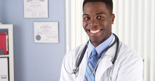 Medico afroamericano allegro che sta nel suo ufficio Fotografia Stock