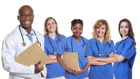 Medico afroamericano bello con il gruppo di nur internazionale Fotografia Stock
