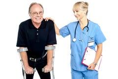 Medico allegro che incoraggia il suo paziente a camminare con le grucce Immagini Stock Libere da Diritti