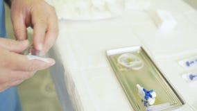 Medico alto vicino delle mani apre lo strumento medico sterile e lo mette sulla tavola video d archivio