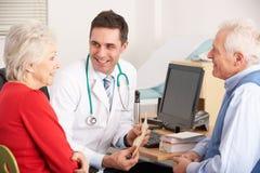 Medico americano che comunica con coppie maggiori Fotografia Stock