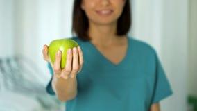Medico amichevole di signora che tiene il primo piano della mela, promozione sana di nutrizione, stante a dieta fotografia stock libera da diritti