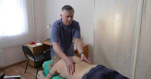 Medico appoggia il massaggio della donna stock footage