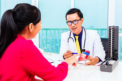 Medico asiatico con il paziente in ambulatorio medico immagini stock libere da diritti