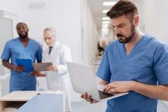 Medico barbuto che utilizza le tecnologie moderne nella clinica Fotografia Stock