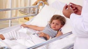 Medico bello che controlla temperatura della bambina video d archivio