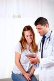 Medico bello e un paziente che osserva per ridurre in pani PC Immagini Stock Libere da Diritti