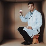 Medico in cappotto con lo stetoscopio in scatola di cartone immagine stock