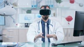 Medico caucasico che indossa una cuffia avricolare di VR nel suo ufficio moderno video d archivio