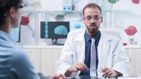Medico caucasico con gli occhiali di protezione dell'AR che mostrano qualcosa ad un paziente stock footage