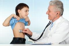 Medico caucasico di fortuna felice con i pazienti Immagini Stock