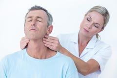 Medico che allunga il suo collo paziente Immagine Stock