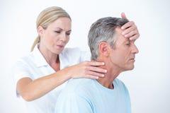 Medico che allunga il suo collo paziente Fotografia Stock Libera da Diritti