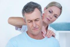 Medico che allunga il suo collo paziente Fotografie Stock Libere da Diritti