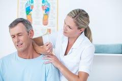 Medico che allunga il suo collo paziente Fotografia Stock