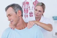 Medico che allunga il suo collo paziente Immagini Stock