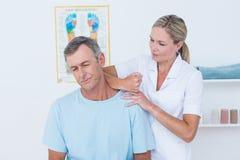 Medico che allunga il suo collo paziente Immagini Stock Libere da Diritti