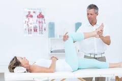 Medico che allunga la sua gamba dei pazienti Fotografia Stock