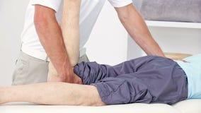 Medico che allunga la sua gamba dei pazienti stock footage