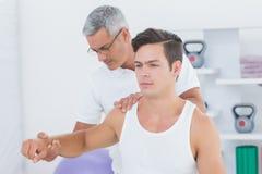 Medico che allunga un braccio del giovane Immagini Stock Libere da Diritti