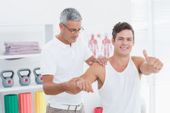 Medico che allunga un braccio del giovane con il pollice su Immagini Stock