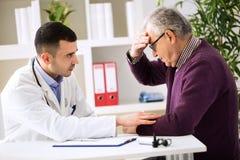 Medico che ascolta il paziente che spiega il suo doloroso fotografie stock