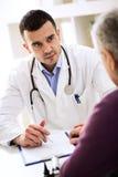 Medico che ascolta il paziente che spiega il suo doloroso immagini stock libere da diritti