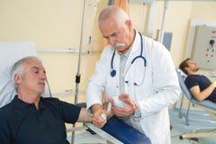 Medico che benda il polso maschio dei pazienti fotografie stock libere da diritti
