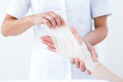 Medico che benda il suo polso paziente fotografia stock