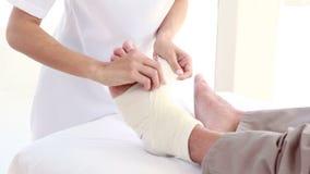 Medico che benda la sua gamba paziente archivi video