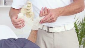 Medico che benda la sua mano dei pazienti stock footage