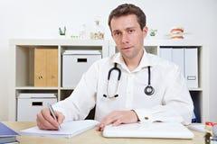 Medico che cattura le note in ufficio Immagini Stock