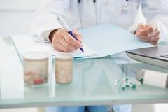 Medico che compila le prescrizioni Immagine Stock