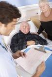 Medico che comunica con coppie maggiori in ospedale immagini stock