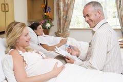 Medico che comunica con diagramma della holding della donna incinta Fotografia Stock