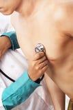 Medico che controlla battimento di cuore paziente Immagine Stock