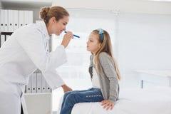 Medico che controlla gli occhi dei pazienti Immagine Stock Libera da Diritti