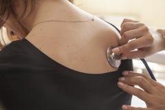 Medico che controlla i polmoni di una giovane donna Immagine Stock