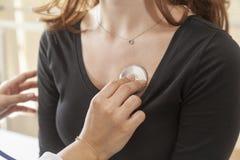 Medico che controlla il cuore di una giovane donna Immagini Stock
