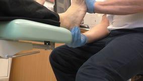 Medico che controlla il piede dell'uomo video d archivio