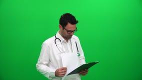 Medico che controlla le cartelle sanitarie video d archivio