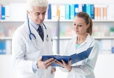 Medico che controlla le cartelle sanitarie Fotografia Stock